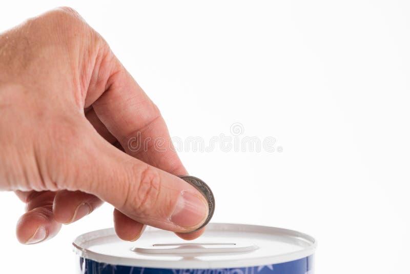 Die männliche Hand, die eine Münze in die Blechdose steckt, spart die Bank lizenzfreie stockfotografie
