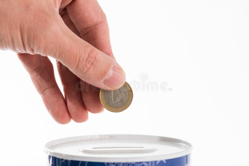 Die männliche Hand, die eine Münze in die Blechdose steckt, spart die Bank lizenzfreies stockbild