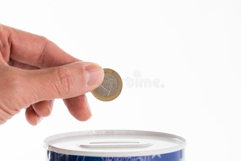 Die männliche Hand, die eine Münze in die Blechdose steckt, spart die Bank stockbild