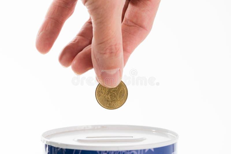Die männliche Hand, die eine Münze in die Blechdose steckt, spart die Bank lizenzfreie stockbilder