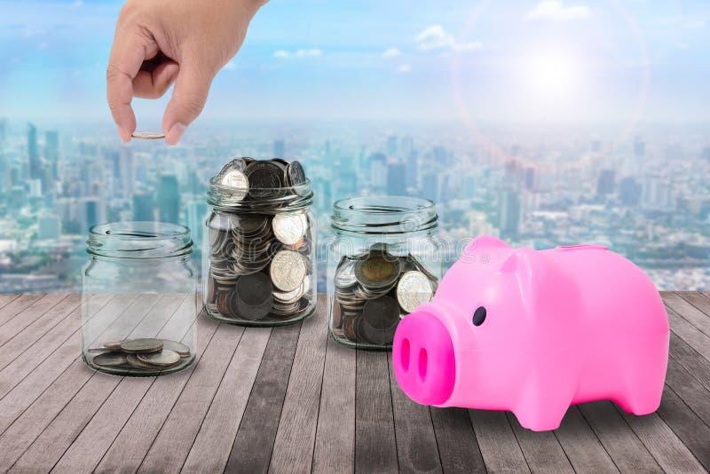 Die männliche Hand, die Geld steckt, prägt in der klaren Flasche, Sparschwein anflehen an lizenzfreie stockbilder