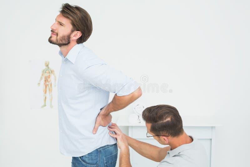 Die männliche Physiotherapeutenuntersuchung bemannt zurück lizenzfreies stockbild