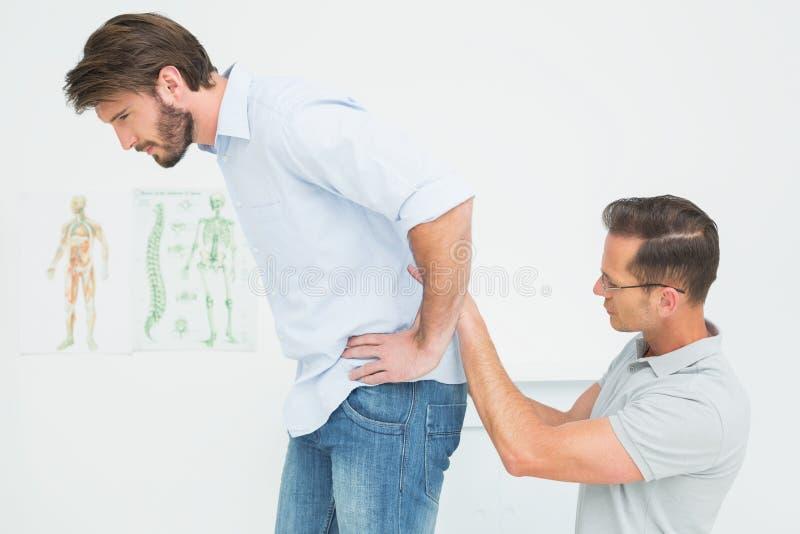 Die männliche Physiotherapeutenuntersuchung bemannt zurück lizenzfreie stockbilder
