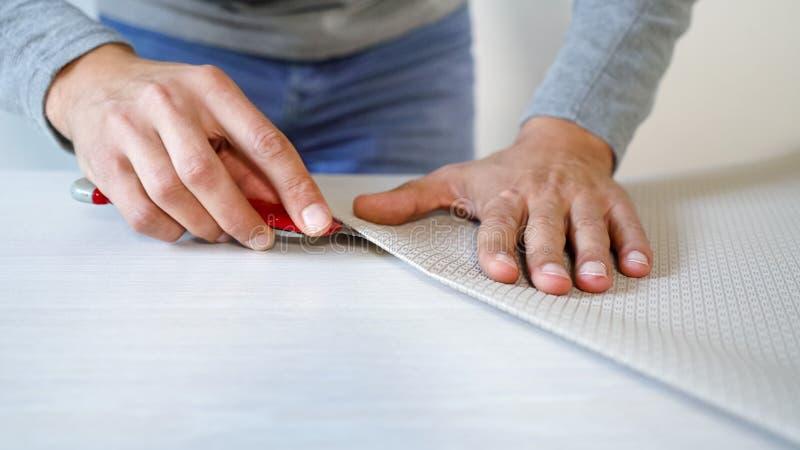 Die männlichen Hände der Nahaufnahme, die neue verbogene Tapete vorbereiten, rollen mit Teppichmesser auf der Innen Tabelle lizenzfreies stockbild
