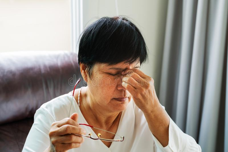 Die müde alte Frau, welche die Brillen entfernt, nach dem Ablesen des Papierbuches massierend mustert Gefühlsunbehagen wegen der  stockfotos