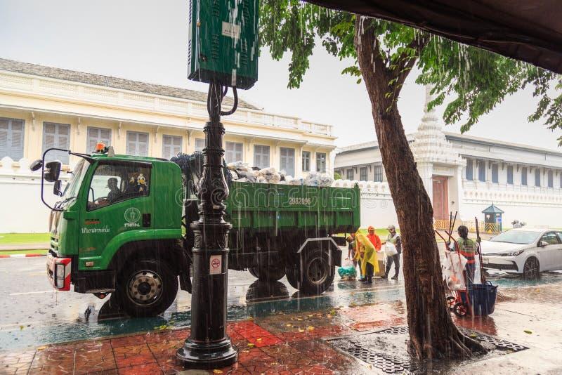 Die Müllmänner führt Aufgaben durch, während der Regen heav fällt lizenzfreie stockfotografie