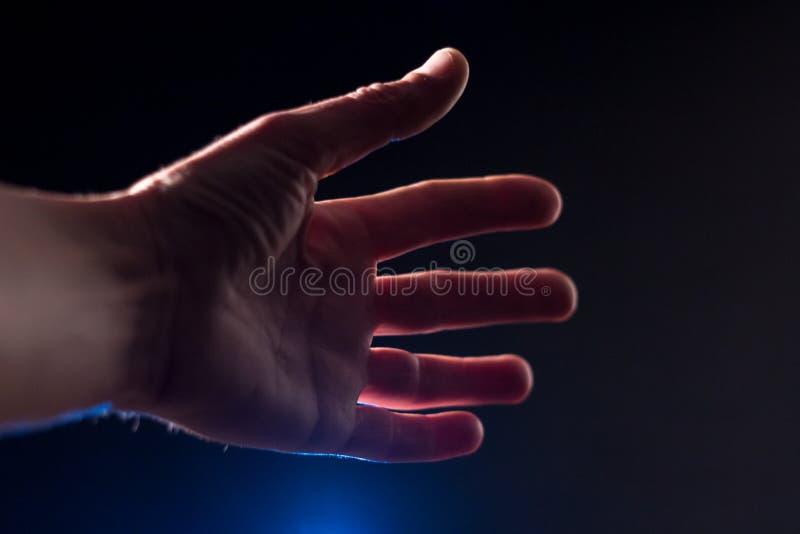 Die Mann ` s Hand ist vorwärts gegen einen dunklen Hintergrund mit einem Blaulicht ausgedehnt Nahaufnahme Flache Schärfentiefe bl lizenzfreies stockfoto