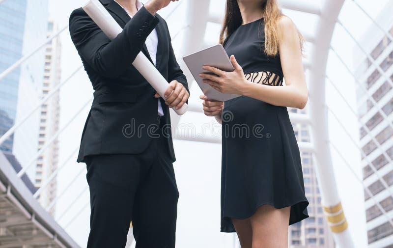 Die Mann- und Frauenwirtschaftsingenieure, die eine Tablette und ein Planarbeiten und -beratung an Standort halten, beginnen oben stockfotos