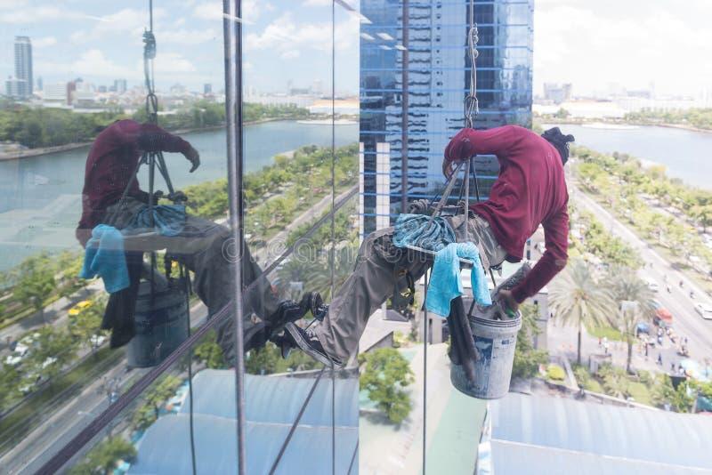 Die Mannarbeitskraft, die das Glasgebäude säubert lizenzfreie stockfotos