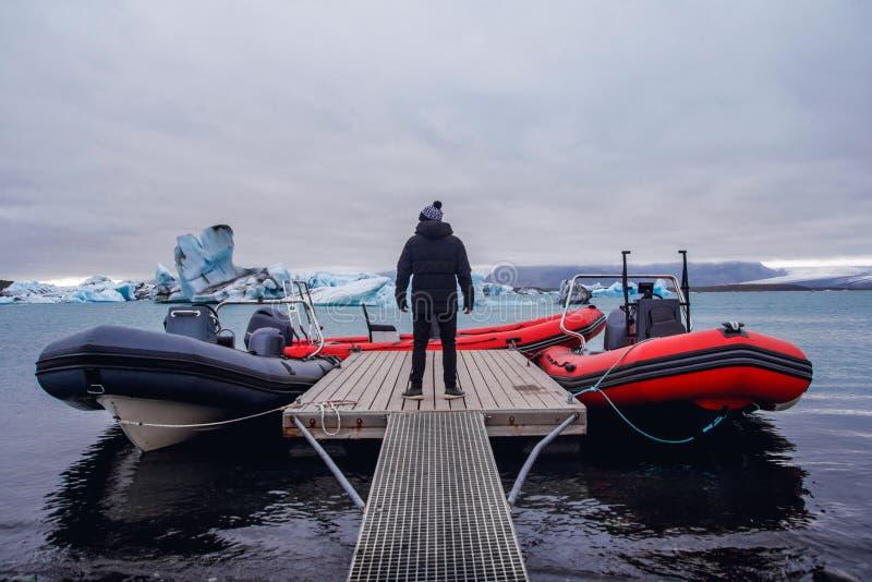 Die Mannstellung auf Pier im Winter Stilvolle Winterkleidung Eisberge in Jokulsarlon-Lagune lizenzfreie stockfotos