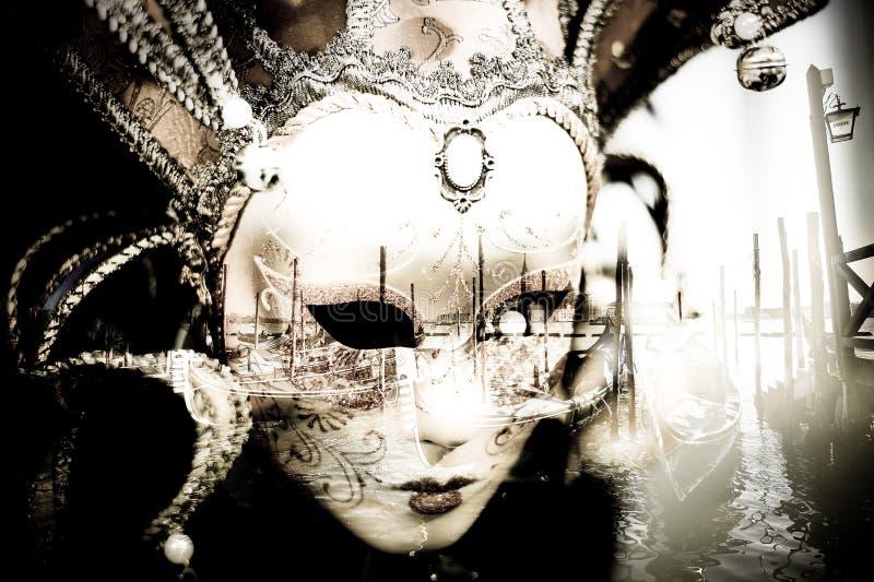 die Maske überblickt die Gondeln auf der venetianischen Lagune im Marktplatz San Marco in Venedig stockbild
