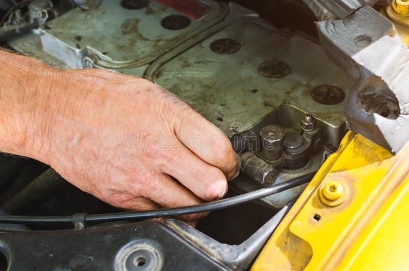Die Mechaniker ` s Hände, die einen Automotor durchführen, überprüfen lizenzfreie stockfotos