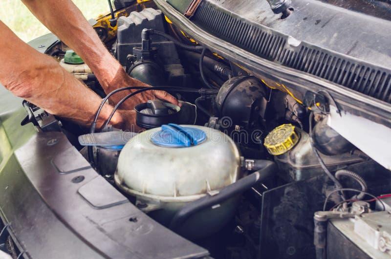 Die Mechaniker ` s Hände, die einen Automotor durchführen, überprüfen stockfoto