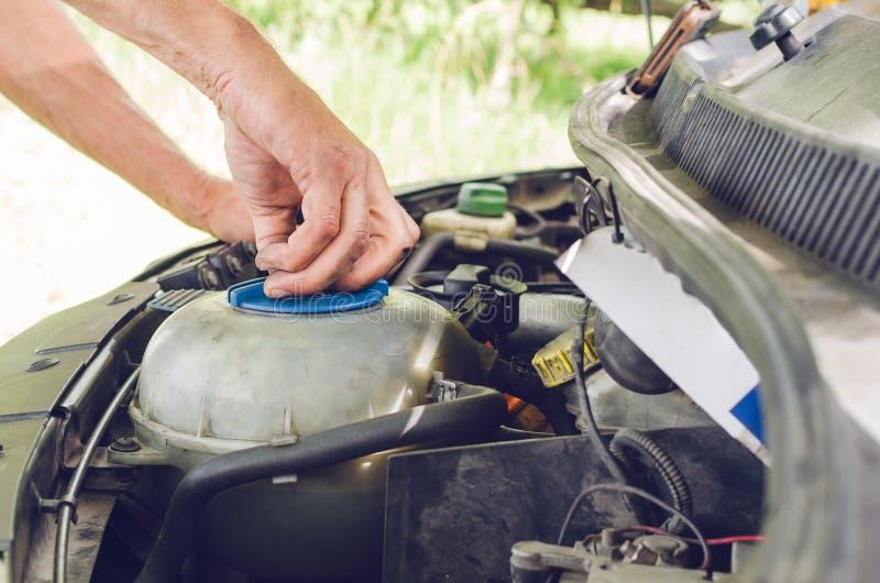 Die Mechaniker ` s Hände, die einen Automotor durchführen, überprüfen stockfotografie