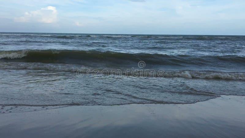 Die Meereswellen, die über Sand zusammenstoßen, setzen ununterbrochen, bewölkter Himmel auf den Strand stock footage