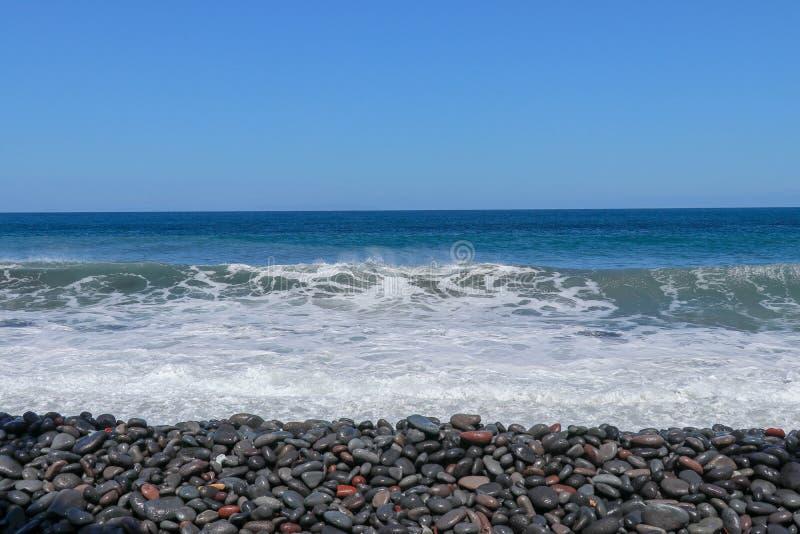 Die Meereswellen die steinige Küste schlagend bewegen Drehung in Gischt wellenartig Schaumiges Meerwasser und Blasen Das Azoren-T stockbild