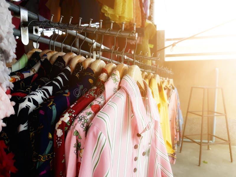 Die mehrfarbige Kleidung, die an der Wäscheleine im Geschäft hängt, ist in der Tageszeit sonnig stockbild