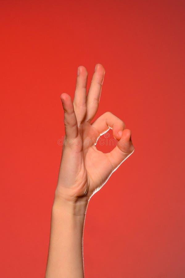Die menschliche Hand zeigt das Zeichen-O.K., welches das Positiv symbolisiert, lokalisiert auf einem roten Hintergrund stockbilder