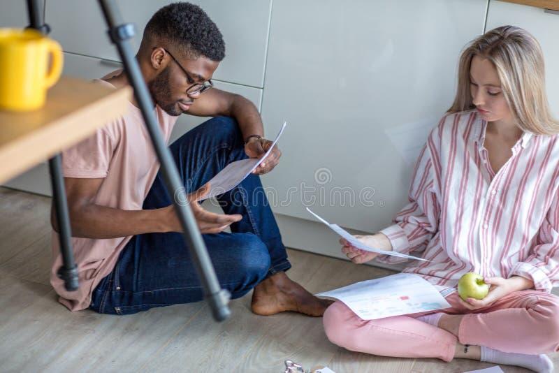 Die Mischrassestudenten, die zusammen auf Küchenboden bereiten sitzen zu Hause sich, zu den Prüfungen vor stockfotos