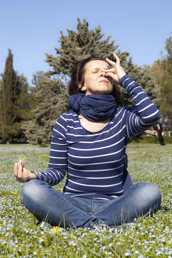 Die mittlere gealterte Frau, die Yoga pranajama tut, trainiert draußen lizenzfreie stockfotos