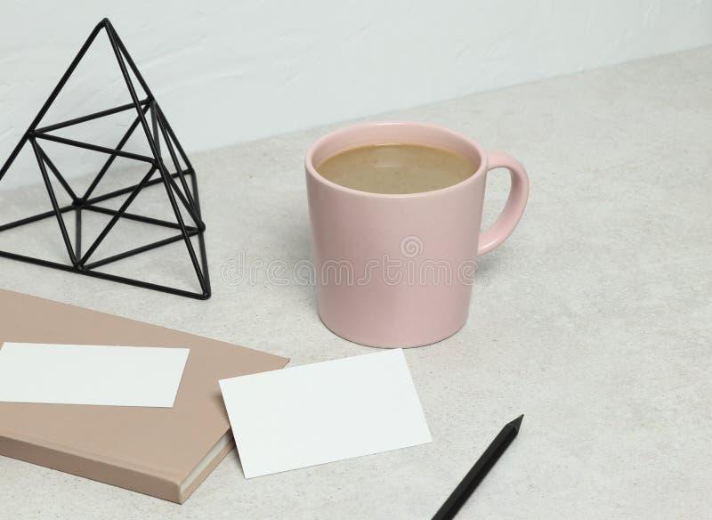 Die Modellvisitenkarte auf Granit mit rosa Buch, Bleistift und Statuette, Tasse Kaffee stockbilder