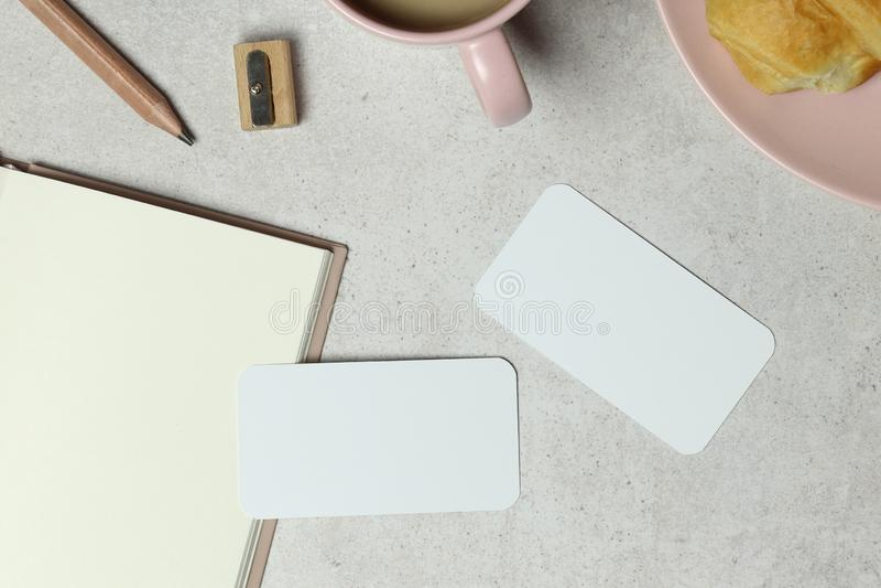 Die Modellvisitenkarte auf Granithintergrund mit Anmerkungsbuchpapier, -Tasse Kaffee und -kuchen, -bleistift u. -bleistiftspitzer stockfoto