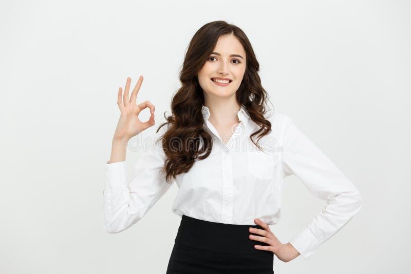 Die moderne schöne Geschäftsfrau, die o.k. darstellt, unterzeichnen vorbei grauen Hintergrund lizenzfreies stockbild