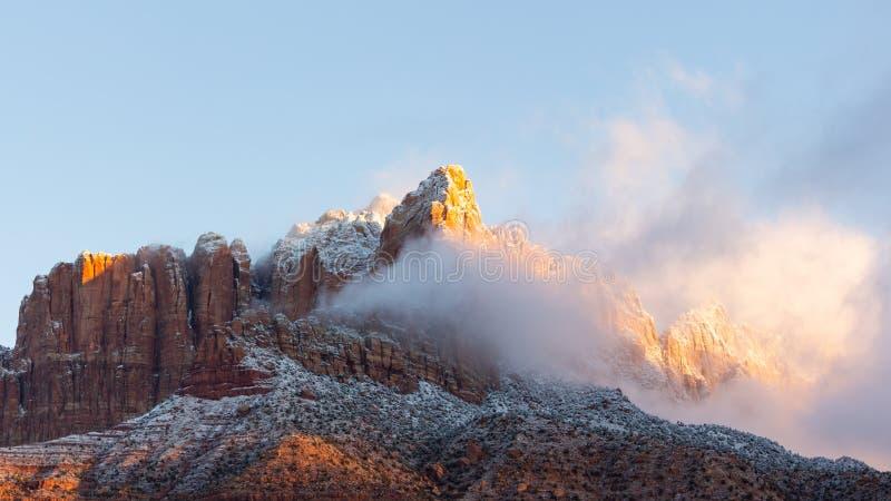 Die Morgensonne fängt an, die Wintersturmwolken weg zu brennen, die vorher von der Nacht auf Mt bleiben Kinesava in Nationalpark  lizenzfreies stockfoto