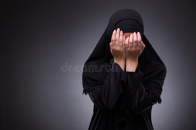 Die moslemische Frau im schwarzen Kleid gegen dunklen Hintergrund lizenzfreie stockfotografie