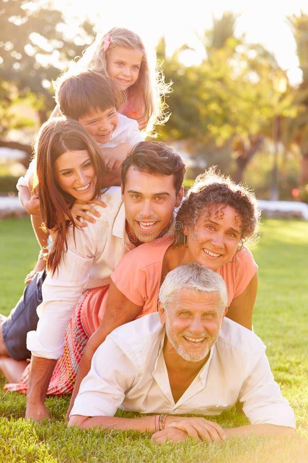 Die multi Generations-Familie, die herein liegt, häufen oben auf Gras zusammen an stockbild