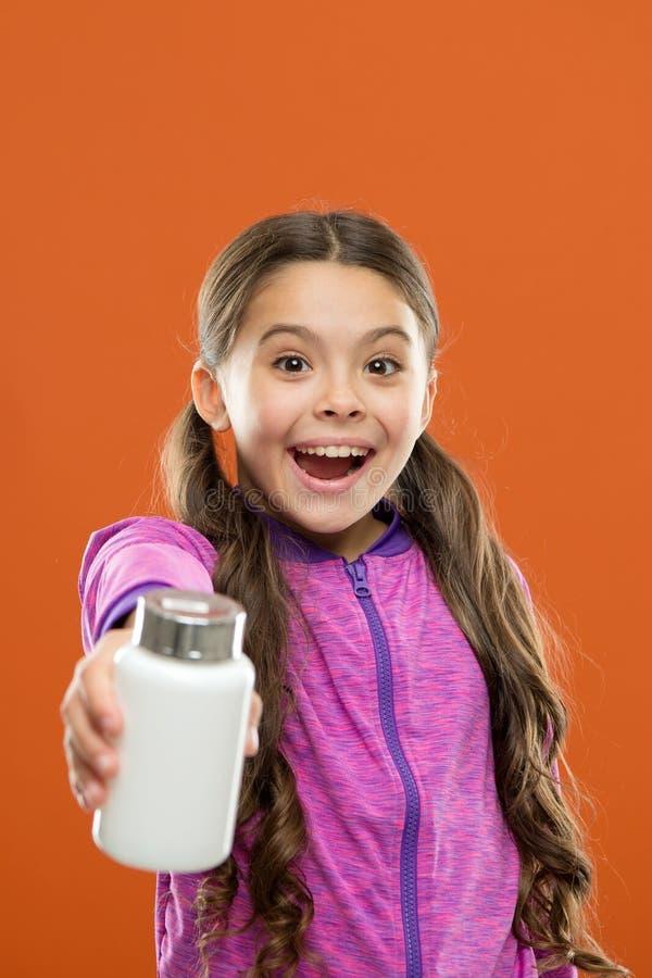 Die Multivitamins der Kinder Nehmenvitaminergänzungen Mädchengriff-Medizinflasche Vitaminkonzept Benötigen Sie Vitaminergänzungen lizenzfreies stockbild