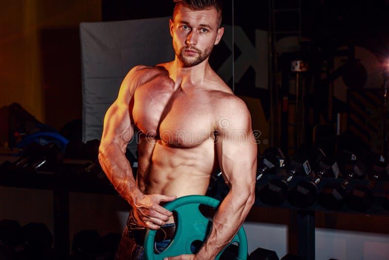 Die muskulösen starken athletischen Männer, die oben pumpen, mischt mit und in der Turnhalle, die ausbilden Hübscher Bodybuilderk stockbild