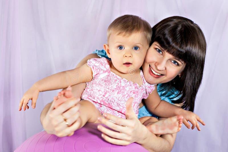Die Mutter mit kleinem Mädchen auf der großen Kugel stockfotografie