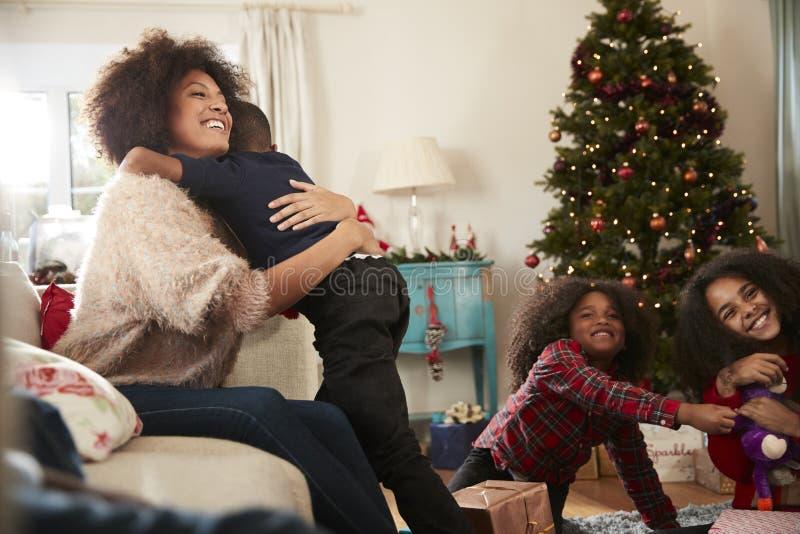 Die Mutter, die Sohn-Umarmung als Familie gibt, feiern Weihnachten zu Hause zusammen stockfoto