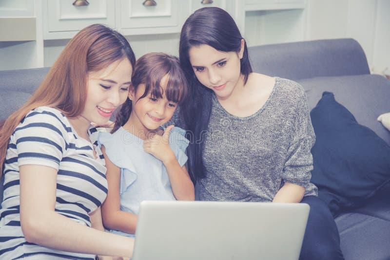 Die Mutter, Tante und Kind, welche die Zeit zusammen lerning ist mit der Anwendung der Laptop-Computers zu Hause mit hat, entspan stockfotos