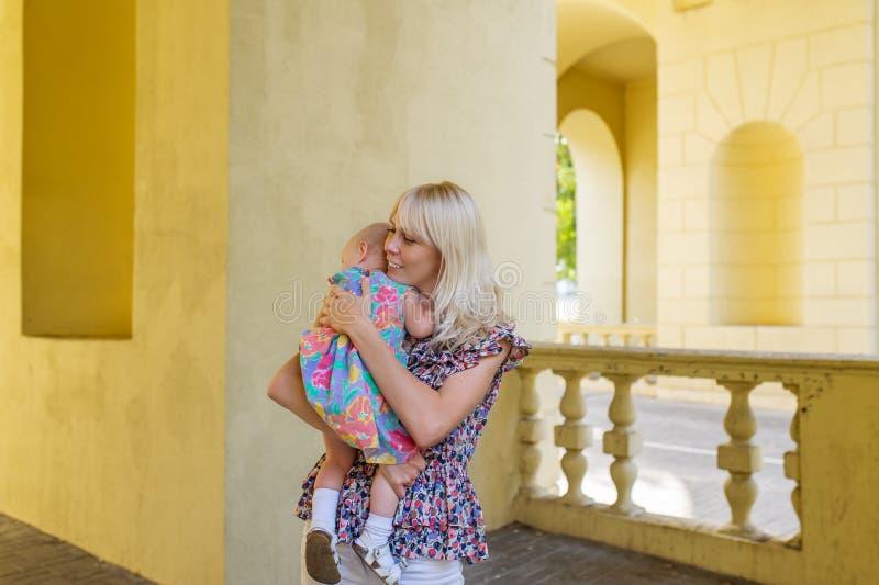 Die Mutter und das kleine Baby, welche die Zeit im Freien an einem warmen Herbsttag verbringt lizenzfreie stockbilder