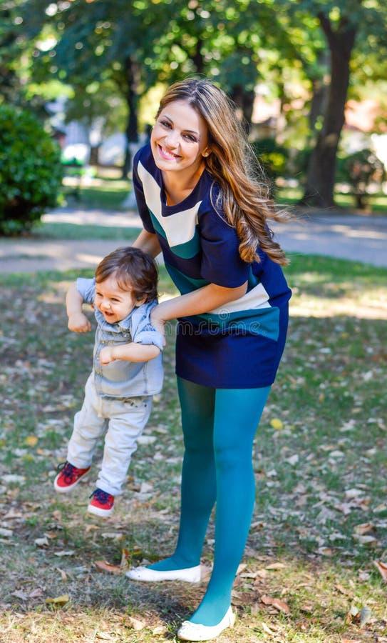 Die Mutter und Sohn, die im Herbst spielen, parken stockfotografie