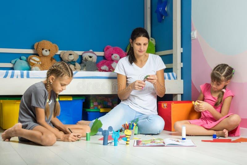 Die Mutter und Töchter, die auf Boden in der Kindertagesstätte sitzen, stellen Figürchen für Fingertheater her lizenzfreie stockfotografie