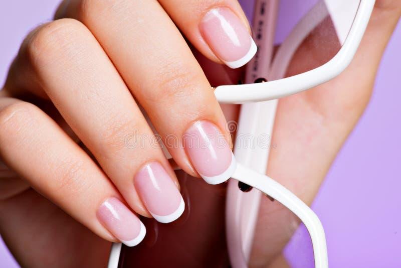 Die Nägel der Frau mit schöner französischer weißer Maniküre stockbild
