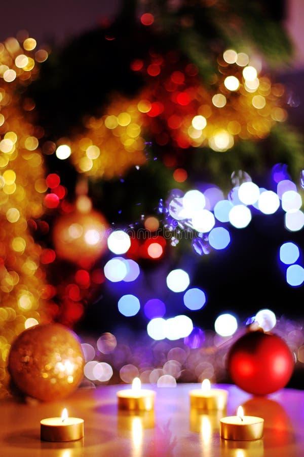 Die Nacht von Weihnachtsabend, beleuchtet goldene Kerzen mit dem funkelnden Baum im Hintergrund stockbild