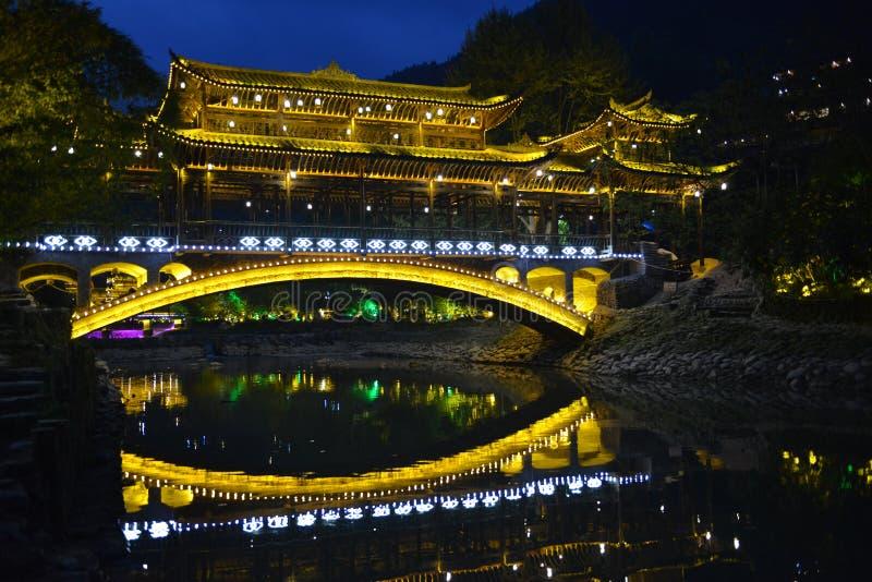 Die Nachtszene der Fengyu-Brücken-Wind-Regenbrücke in Xijiang Qianhu Miao Village lizenzfreie stockbilder