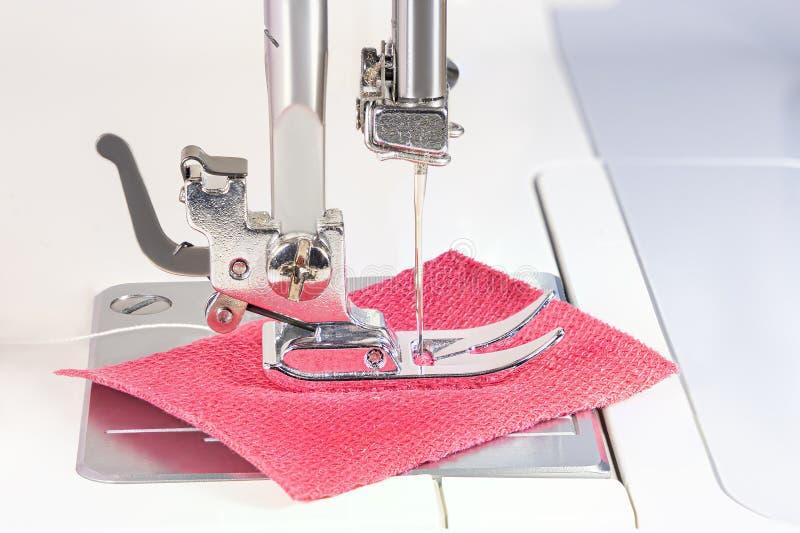Die Nadel der Nähmaschine näht roten Stoff Der Fuß der Maschine wird mit Staub und Fasern umfasst lizenzfreies stockbild