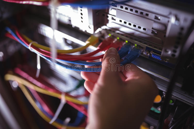 Die Nahaufnahme des Technikers Fleckenkabel in einem Gestell verstopfend brachte Server an lizenzfreie stockfotografie