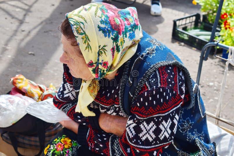 Die neigende Großmutter sitzt und wartet auf Käufer stockfoto