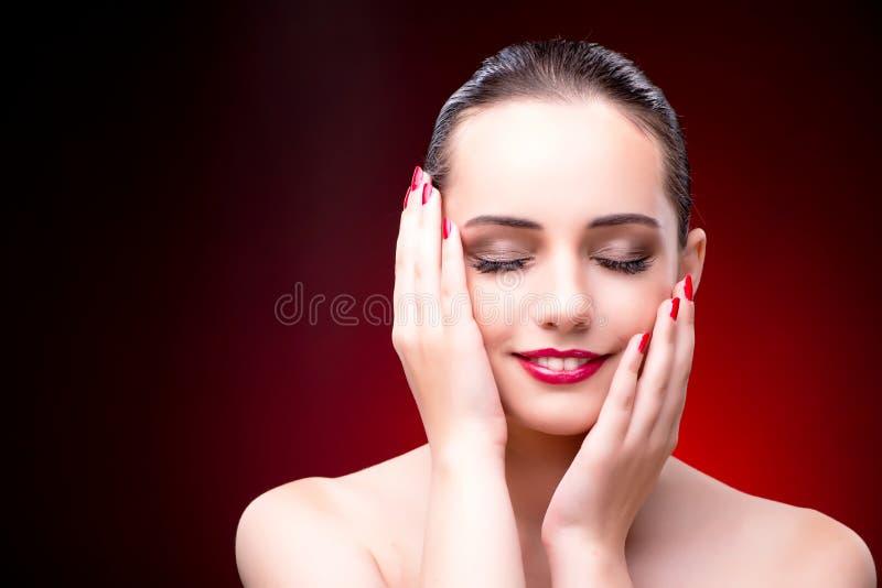 Die nette Frau gegen den roten Hintergrund lizenzfreie stockfotografie
