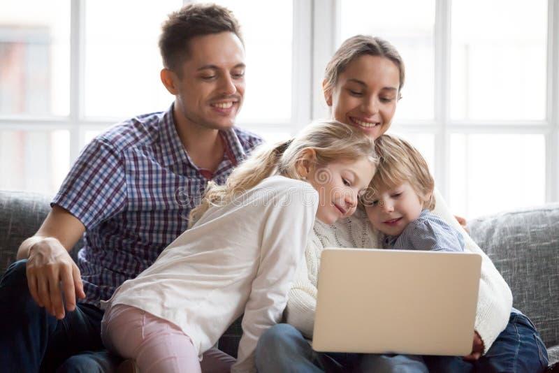 Die neugierigen netten Kinder, die auf Laptop unter Verwendung des Computers mit spähen, schneiden lizenzfreie stockfotos