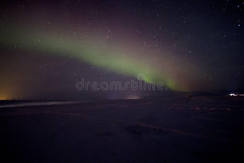 Die Nordlichter im bewölkten Himmel in Island lizenzfreie stockfotos