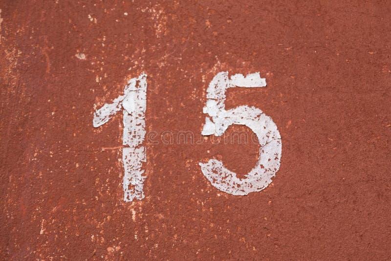 Die Nr. fünfzehn im Weiß auf einer alten roten Wand stockfotografie