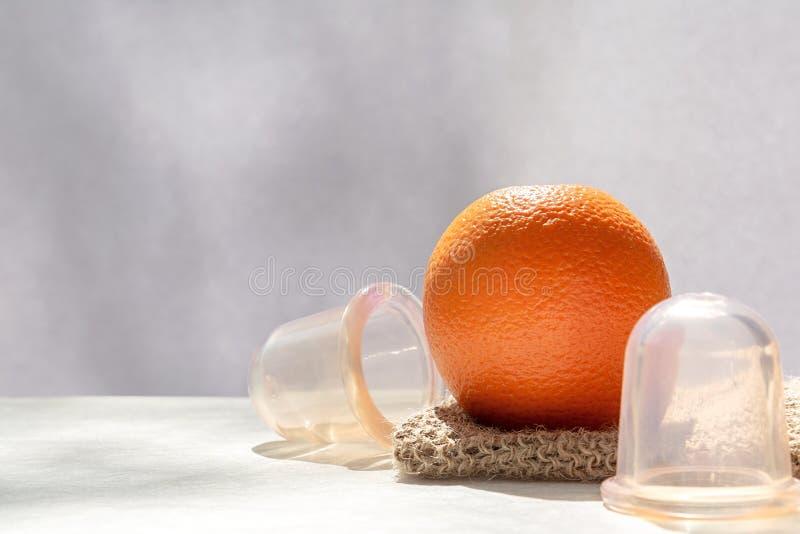 Die orange Lügen auf einem Maschenwaschlappen, der von den Naturfasern und nahe bei ihm gemacht wird, sind Vakuumbanken lizenzfreies stockfoto