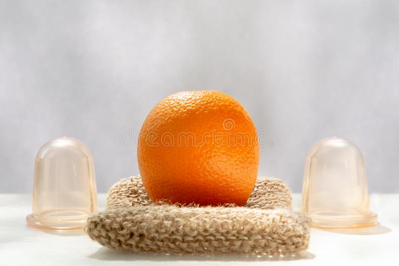 Die orange L?gen auf einem Maschenwaschlappen, der von den Naturfasern und nahe bei ihm gemacht wird, sind Vakuumbanken stockbild